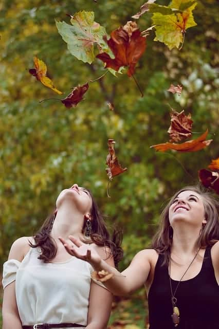 girls tossing fall leaves into the air