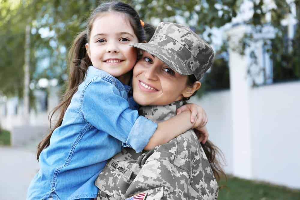 military mom holding daughter